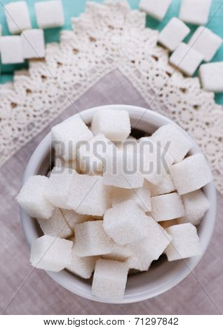 Refined sugar in color bowl on color wooden background