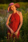 stock photo of beatitudes  - Young woman in a hat among wildflowers at sunset - JPG