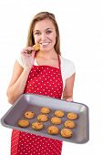 picture of homemaker  - Pretty homemaker showing hot cookies on white background - JPG
