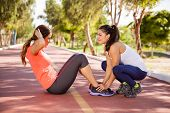 pic of crunch  - Two female friends working out together and doing some crunches outdoors - JPG