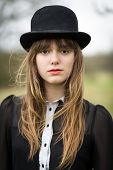 picture of nylons  - Portrait of a beautiful young woman wearing a black dress nylons boots and a bowler hat standing in a country farm field hair blowing in the wind - JPG