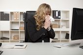 stock photo of blowing nose  - Businesswoman suffering from a cold or hay fever blowing her nose at her desk with a tissue as she continues reading the screen of her computer - JPG