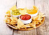 stock photo of nachos  - nachos with various sauces on wooden table - JPG