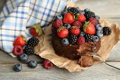 stock photo of chocolate spoon  - Tasty chocolate cake with different berries on wooden table - JPG