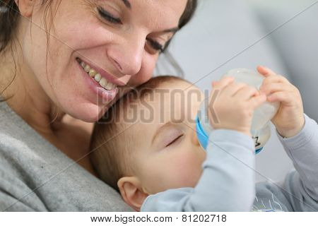 Mother and baby boy holding baby bottle