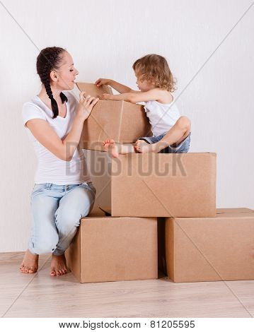 Family Sit In A Room On The Boxes.