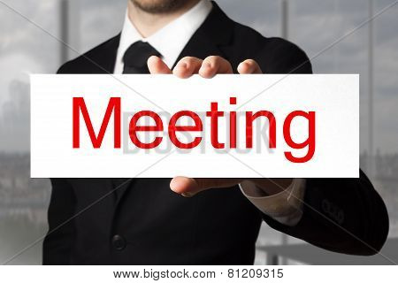 Businessman In Office Holding Sign Meeting