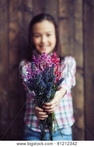 Little girl showing bunch of fresh wildflowers