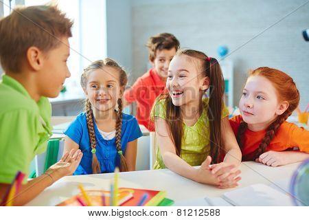 Happy friends talking during break in school