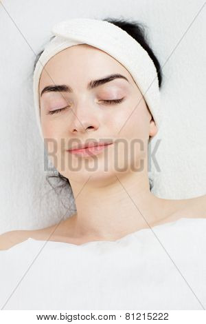 Satisfied young woman with closed eyes portrait in beauty parlour