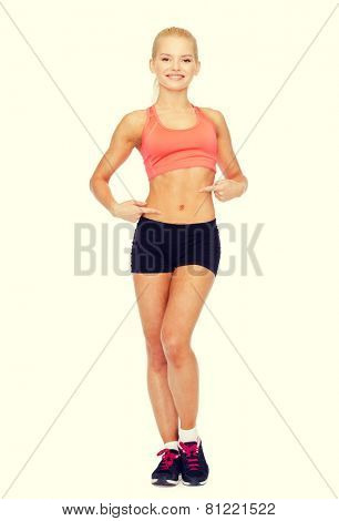 fitness, exercise and diet concept - smiling beautiful sporty woman pointing at her six pack