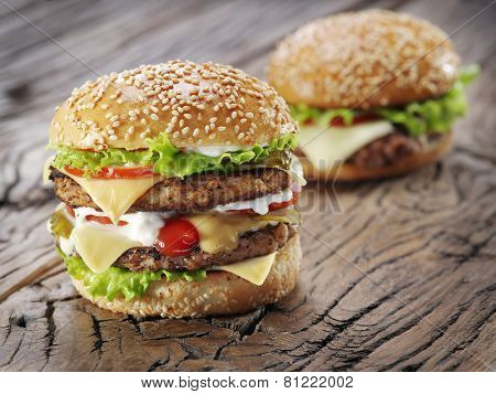 Two hamburgers on old wooden table.
