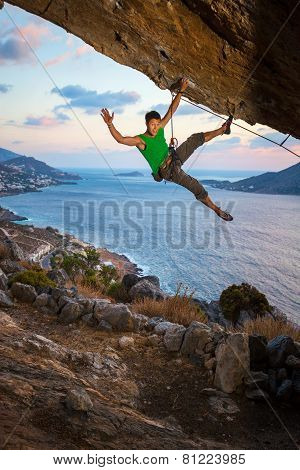 Rock climber waving his hand while climbing