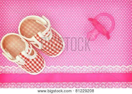 Baby shoes and pink pacifier on polka dots background with copy space