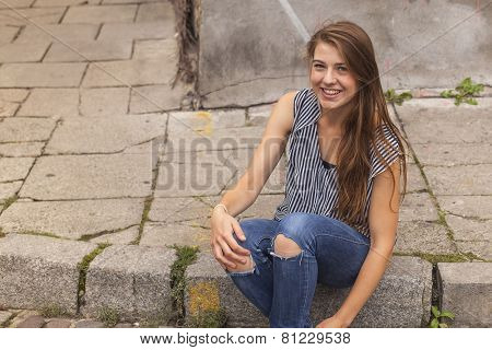 Young cute hipster girl sitting on curb on the street in old town.