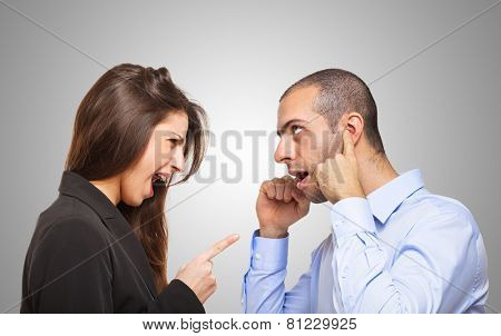 Man covering his ears in front of an angry woman