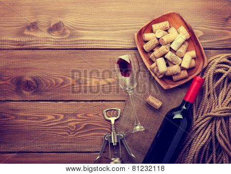 Red wine bottle, glass and corkscrew on wooden table background with copy space. Retro toned