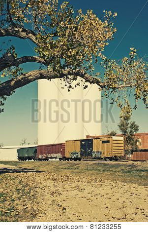 Rail cars sitting on a siding beside grain silos.