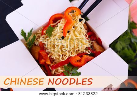 Chinese noodles with vegetables in takeaway box and space for your text