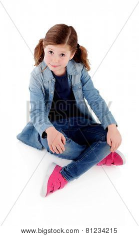 Adorable little girl sitting on the floor with denim shirt isolated on a white background