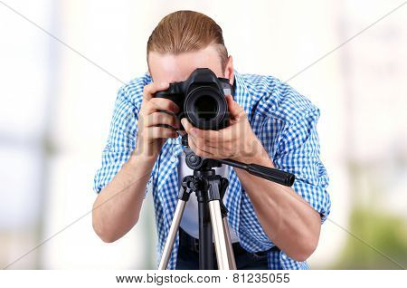 Handsome photographer with camera on tripod indoors