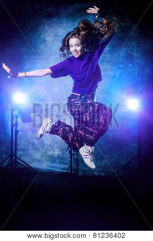 Beautiful hip-hop dancer jumping over grunge background.