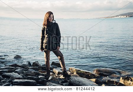 Woman Standing On Coastline Near The Sea