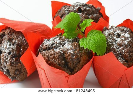 detail of four chocolate muffins in red paper baskets