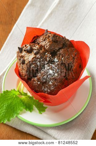 cupcake with chocolate chips, wrapped in the red paper basket and served on the plate with fabric linen