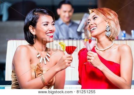 Asian women drinking cocktails in fancy bar