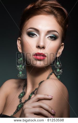 Beautiful red-hair girl with perfect skin and bright green makeup. Beauty face