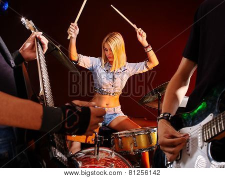Musical group playing in night club. Girl with drum