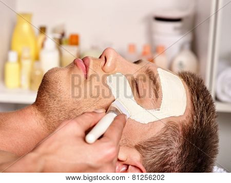 Man with clay facial mask in beauty spa. Male face close up
