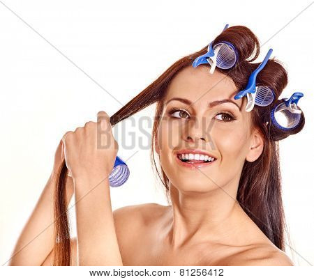 Happy beautiful woman wear hair curlers on head. Girl has bare shoulders
