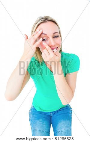 Happy blonde applying contact lens on white background