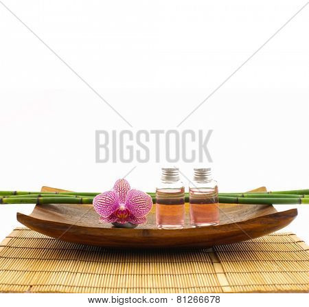 SPA setting with orchid ,oil, grove in bowl on mat