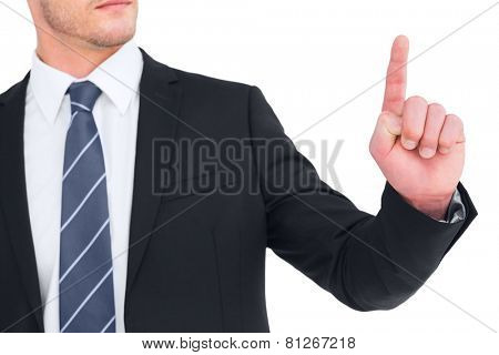 Unsmiling businessman pointing his finger on white background