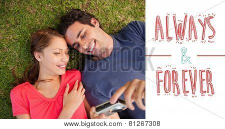 Two smiling friends looking at photos on a camera against always and forever