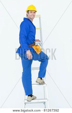 Full length portrait of repairman climbing step ladder over white background