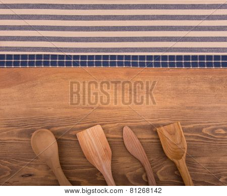 Blue and off white kitchen towels on dark wood background with wooden kitchen utensils, and room for text in center