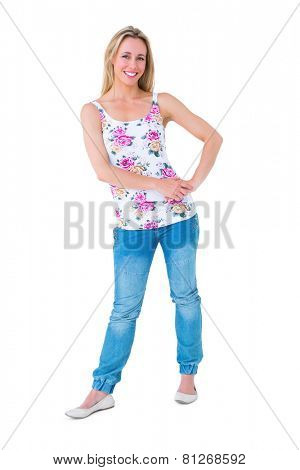 Smiling blonde posing with hand on hip on white background
