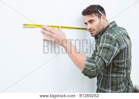 Side view of male carpenter measuging white wall with measure tape at home