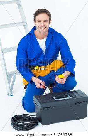 Portrait of happy electrician holding multimeter over white background