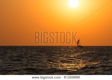 Sail Boat Is Sea Waves Against Bright Sunset Glow