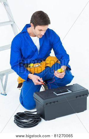 Handsome electrician using multimeter over white background