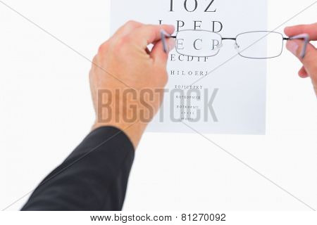 Glasses held up to read eye test on white background