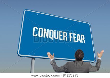 The word conquer fear and businessman posing with arms raised against blue sky