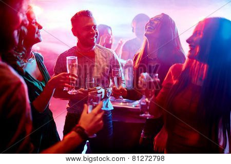 Ecstatic friends with champagne talking at party in night club