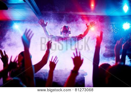 Male deejay in headphones and sunglasses looking at dancing crowd