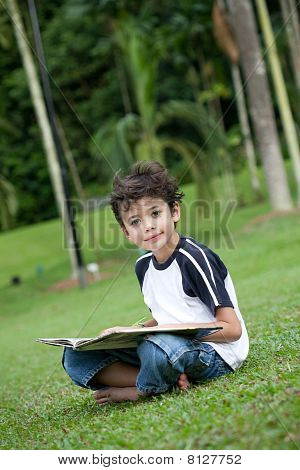 Young boy with book in park